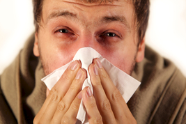 Man with allergies blowing nose