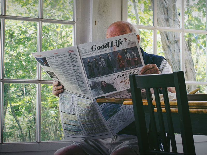 Older adult reading a newspaper